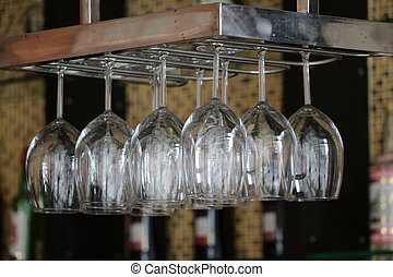 Glass for put wine hanging upside down on a rail at the counter bar.