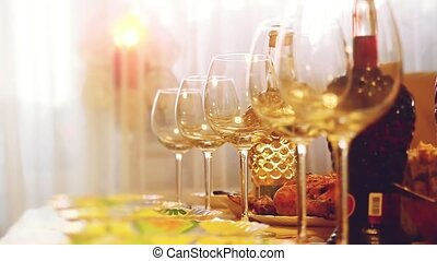 Glass glasses on a table in a restaurant, banquet table, glasses of wine stage lighting. Changes focus to blurred with blurred bokeh in slow motion. 1920x1080