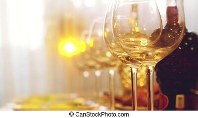 Glass glasses on a table in a restaurant, banquet table, glasses of wine stage lighting. Changes focus to blurred with blurred bokeh in slow motion.