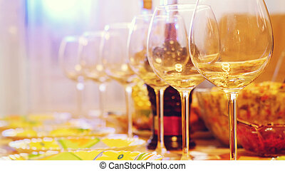 Glass glasses on a table in a restaurant, banquet table, glasses of wine stage lighting.