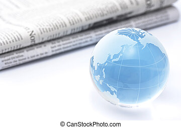 Glass globe and newspaper