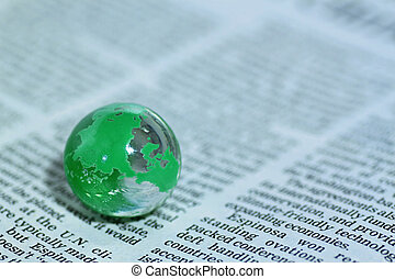 Glass globe over newspaper