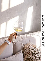 Glass goblet with white wine in a woman's hand against the background of a gray wall