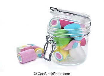 glass jar full of colorful shamallows on white background