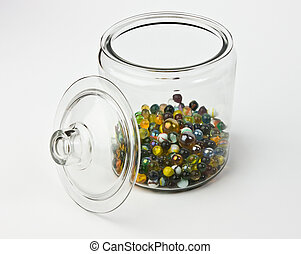 Glass jar half full of colorful glass marbles on a white...