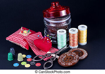 Glass Jar, Neddle Case, Spools, Buttons, Scissors and Thimbles on Black.