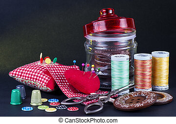 Glass Jar, Nedle Case, Spools, Buttons, Scissors and Thimbles on Black.