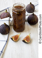 Glass jar of fig jam and fresh figs on white wooden background, side view. Close-up.