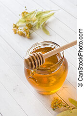 Glass jar of honey, Linden flowers on light background