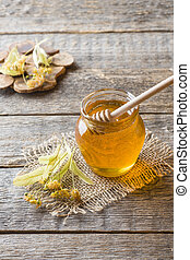 Glass jar of honey, Linden flowers on wooden background.