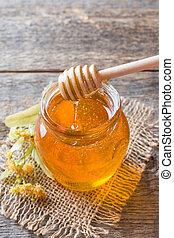 Glass jar of honey, Linden flowers on wooden background.