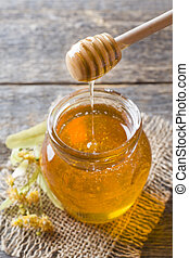 Glass jar of honey, Linden flowers on wooden background