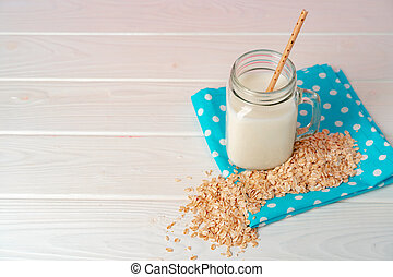 Glass jar of oat vegan milk with oat flakes on white wooden table