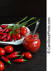 Glass jar of tomato sauce with fresh ingredients
