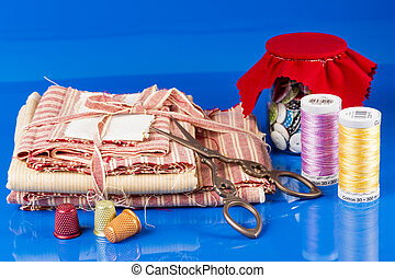 Glass Jar, Scissors, Thimbles and Spools Isolated on Blue.