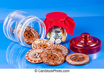 Glass Jar with Buttons Isolated on Blue.