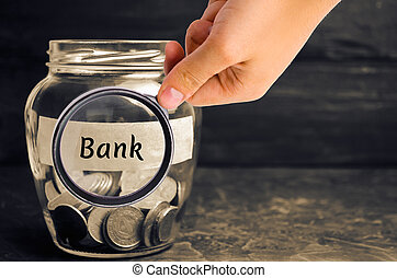 """Glass jar with coins and the inscription """"Bank"""". Deposits, ..."""