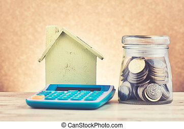 glass jar with coins, calculator and home replica on wooden desk for home loans concept