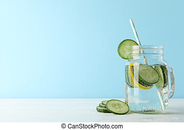 Glass jar with cucumber water on white table, space for text