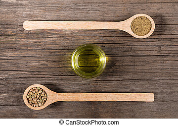 Glass jar with hemp oil and two wooden spoons with cannabis grains and flour on old wooden boards.