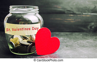 """Glass jar with money and the inscription """" Valentine's Day."""" The accumulation of money for the holiday. Savings on the purchase of gifts for loved ones. The 14th of February"""