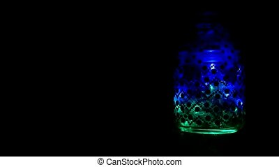Glass jar with New Year's sparkling multi-colored lights, the new year 2019, Christmas, copy space, decoration, design