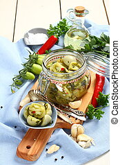 glass jar with pickled green tomatoes prepared for winter