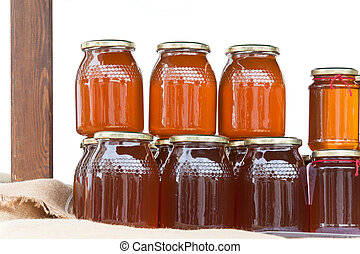 Glass jars with honey on a table isolated