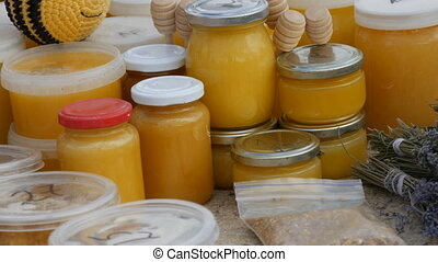 Glass jars with honey, wax and honeycomb at the farmers fair.