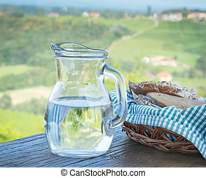 Glass jug with water and bread