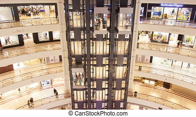 glass lifts in Shopping mall time-lapse. pan up