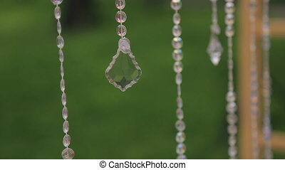Glass long garlands hanging in forest on wedding day outdoors.
