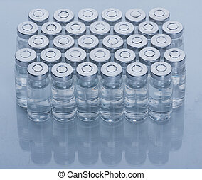Glass medical ampoule vial for injection. Medicine is dry white drug penicillin powder or liquid with of aqueous solution in ampulla. Close up. Bottles ampule with aluminum cap on backgrounds gray.