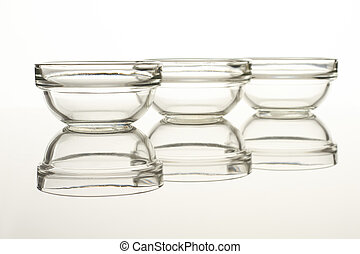 Glass mixing bowl set. Reflective surface. Isolated on...