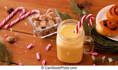 christmas, winter holidays and seasonal drinks concept - glass mug with eggnog and candy cane decoration, sweets and aromatic spices on wooden background over snow falling