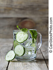 Glass mug with cold fresh lemonade with cucumber and ice