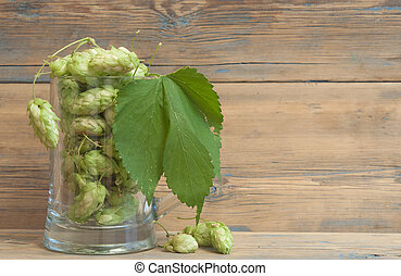 Glass mug with hops on wooden background
