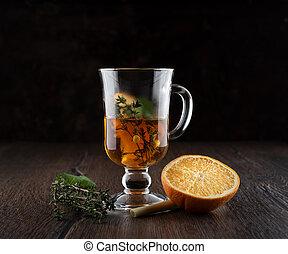 Glass mug with vitamin tea. Vitamin tea ingredients on a wooden table.