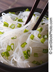 Glass noodles with green onions in a bowl macro. Vertical