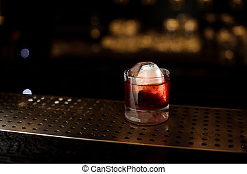 Glass of a Boulevardier cocktail on the steel wooden bar counter