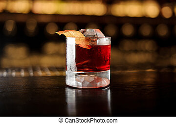 Glass of a Boulevardier cocktail with orange zest on the steel and wood bar counter