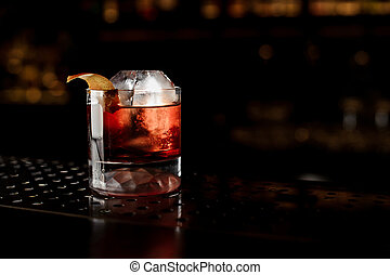 Glass of a Boulevardier cocktail with orange zest on the steel bar counter