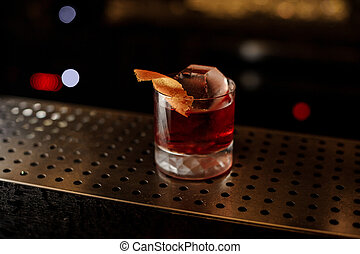 Glass of a Boulevardier cocktail with orange zest on the steel wooden bar counter