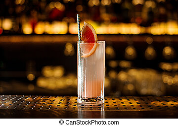 Glass of a cocktail with grapefruit on the wooden steel bar counter