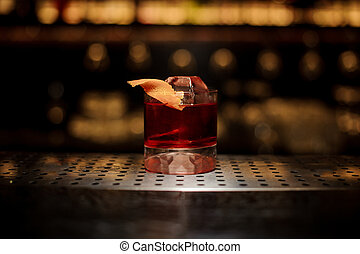 Glass of a delicious Boulevardier cocktail with orange zest on the steel wooden bar counter