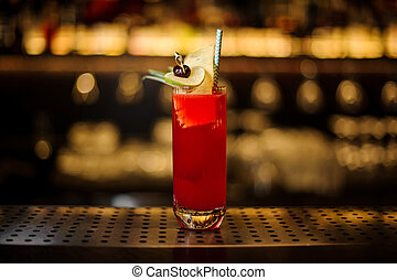 Glass of a Hurricane Punch cocktail on the wooden steel bar counter