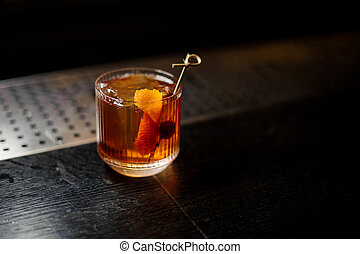 Glass of a Old Fashioned cocktail on the wooden steel bar counter