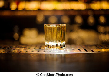Glass of a Rusty Nail cocktail on the wooden steel bar counter