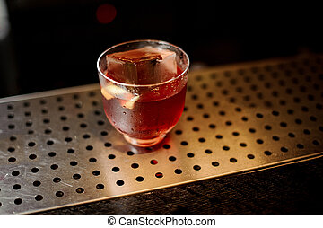 Glass of a Vieux Carre cocktail on the steel bar counter