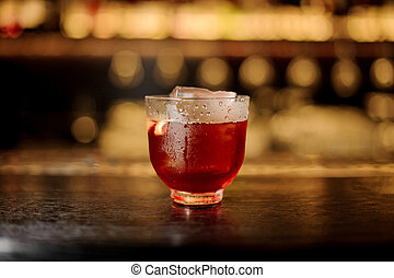 Glass of a Vieux Carre cocktail on the wooden bar counter - ...